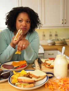 a woman snacking on lots of junk food at her kitchen table